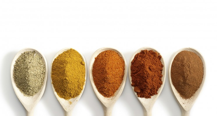 various kinds of spices in wooden spoons